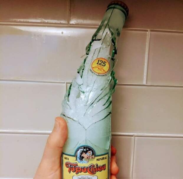 лопнувшая стеклянная бутылка с замороженной водой