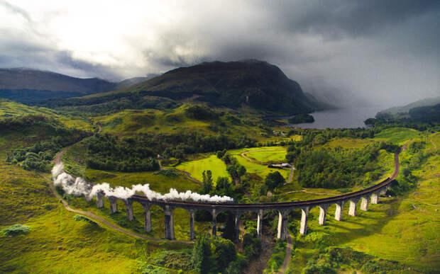 Паровоз едет по виадуку Гленфиннан в Шотландии, где смались фильмы о Гарри Поттере.