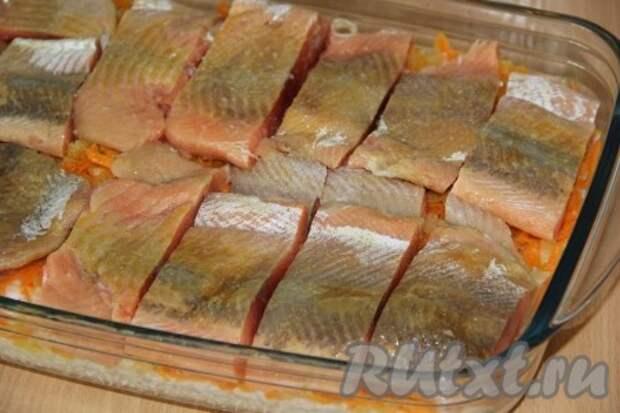 Горбушу нарезать на порционные кусочки, посолить и поперчить по вкусу. Выложить рыбу поверх риса и овощей.