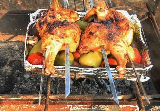 Заворачиваем курицу в фольгу и кладем на мангал