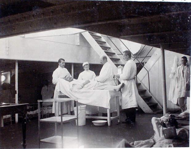 24. Старший врач И. Х. Дзирне (третий слева), сестра милосердия, младший врач В. П. Ивакин - справа крайний перевязывают больного в палате № 2 (на перевязочном пункте). 1901