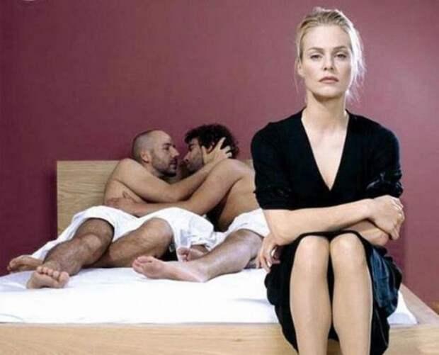 Два мужчины в постели в обнимку и недовольная женщина