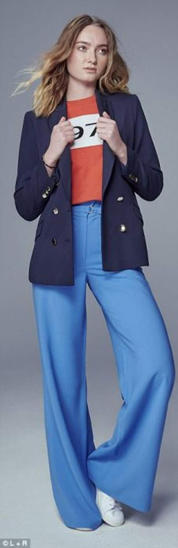 Удлиненный темно-синий пиджак с голубыми брюками и белыми кедами.