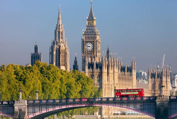 Красный двухэтажный автобус едет по Ламбетскому мосту. На фоне видны Вестминстерский дворец и Биг Бен. Лондон