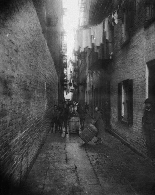 circa 1890:  Children play with barrels in an alley between tenement buildings in Gotham Court, 38 Cherry Street, New York City.  (Photo by Jacob A. Riis/Museum of the City of New York/Getty Images)