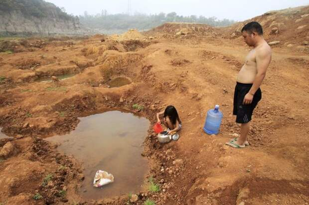 25. Папа с дочкой собирают воду из лужи на месте высохшего водохранилища, уезд Баофэн загрязнение, китай, экология