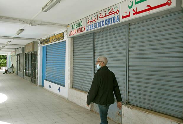 На фото: мужчина проходит мимо закрытых магазинов. Тунис во время действия общенаицонального карантина в период пандемии коронавируса COVID-19.