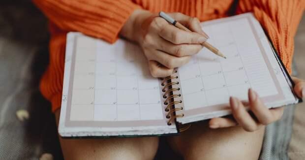 Девушка что-то записывает в ежедневник карандашом