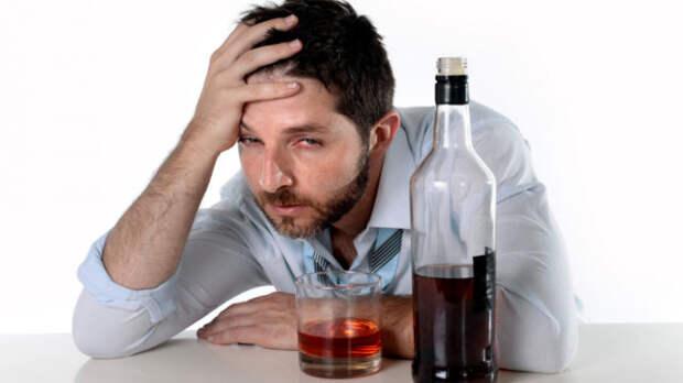 пьяный мужчина сидит за столом с бутылкой