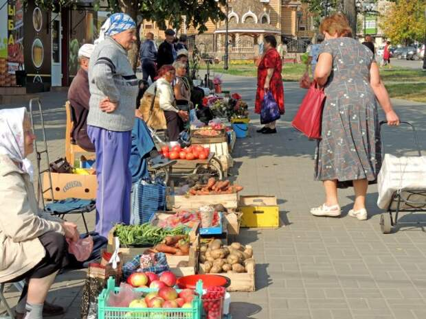 Senior women sell vegetables and fruits from his garden on the pavement of city street