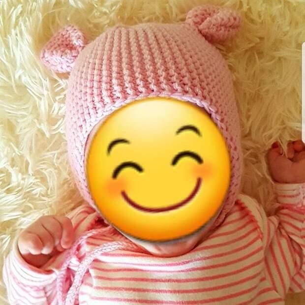 ребенок в розовом со смайликом, закрывающим лицо