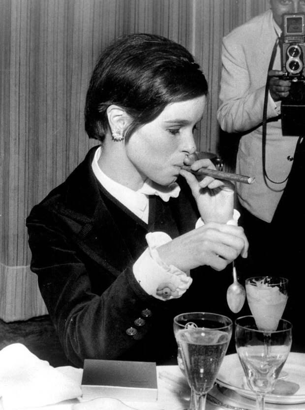 Джеральдина Чаплин прикуривает сигару за столом во время Каннского кинофестиваля, 1967 год.