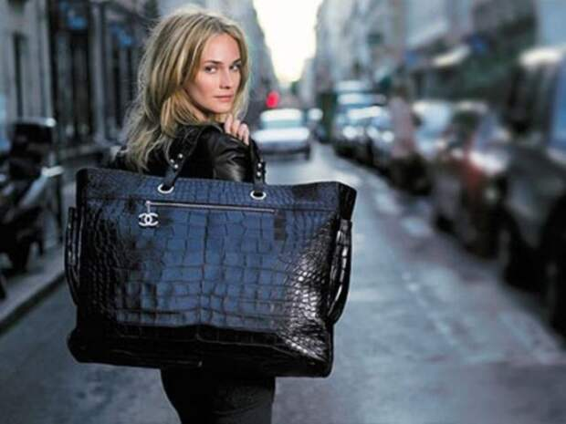 блондинка с большой черной сумкой в руке