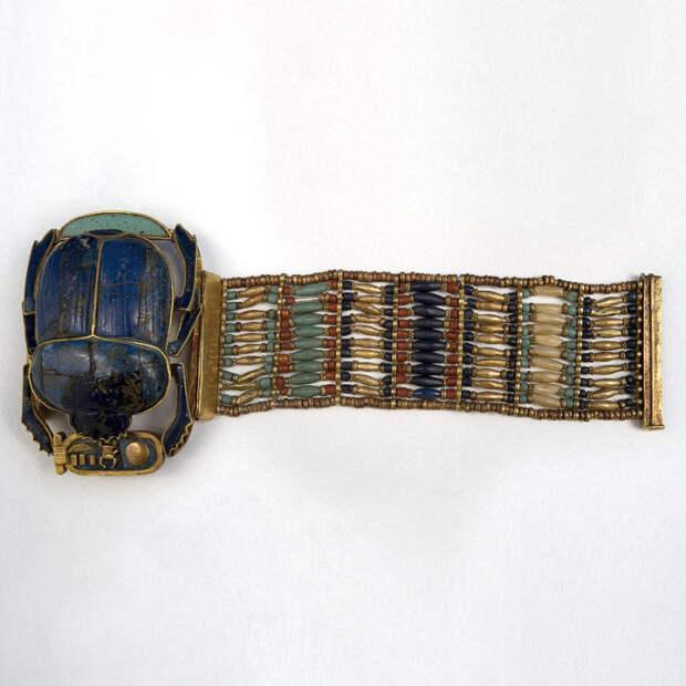 Составлен из золота, электрума и синего стекла.