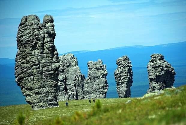 13. Плато Маньпупунёр Этот уникальный геологический памятник природы находится в Троицко-Печорском районе Коми и включает в себя семь огромных каменных исполинов высотой от 30 до 42 метров, которые известны также как столбы выветривания или мансийские болваны. В переводе с мансийского Маньпупунёр обозначает «Малая гора идолов». По одной из местных легенд шесть великанов гнались за манси и уже почти нагнали их, как вдруг перед ними появился шаман с белым лицом по имени Ялпингнер. Он поднял вверх руку и успел произнести заклинание, после которого все великаны окаменели, но и сам Ялпингнер тоже превратился в камень. С тех пор так они и стоят друг против друга.