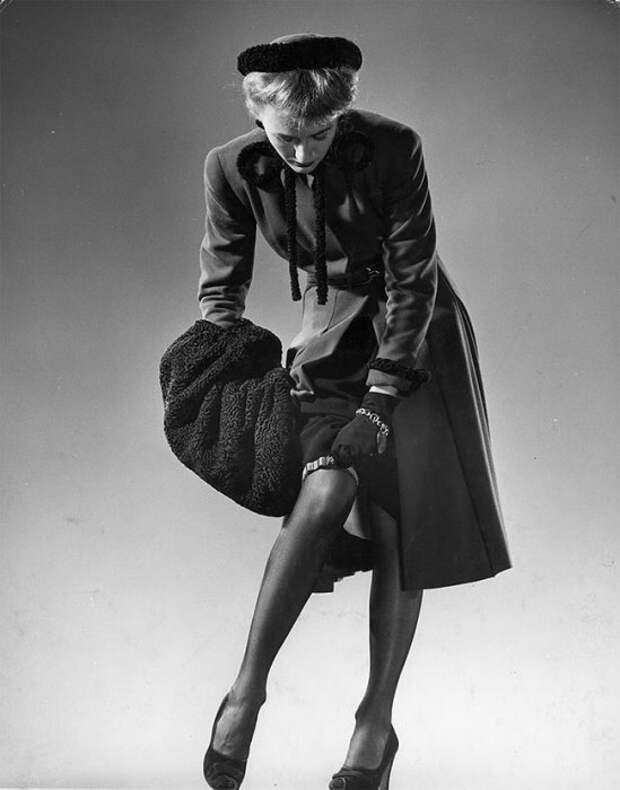 Модель в черных чулках, приталенном черном платье, меховой шляпке и с меховой муфтой поправляет подвязки, 1946 год.
