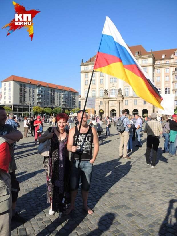 Дарья и немец держат флаг, наполовину немецкий, наполовину русский. Фото: Дарья АСЛАМОВА