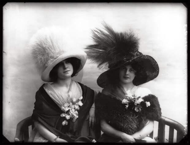 Модницы в шляпках позируют перед фотографом.
