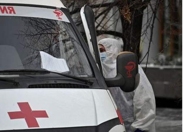 A medical specialist wearing personal protective equipment (PPE) speaks with a driver of an ambulance outside a hospital amid the outbreak of the coronavirus disease (COVID-19) in Omsk, Russia October 28, 2020. REUTERS/Alexey Malgavko