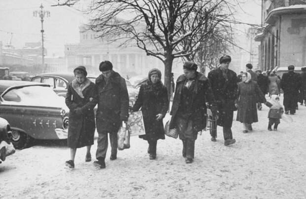 Люди, идущие по Театральной площади, вдоль гостиницы Метрополь.