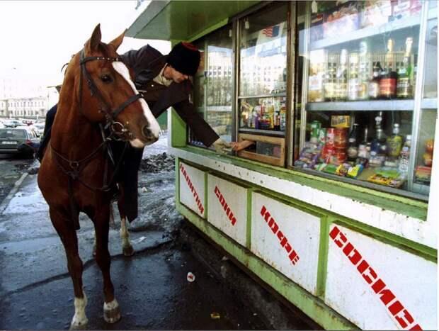 Казак на лошади покупает бутылку водки в ларьке во время парада на День Святого Патрика. Москва. РФ. 1994 год.