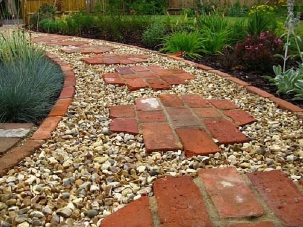Садовые дорожки из красного кирпича и мелкой гальки популярны за счёт своей долговечности и практичности.