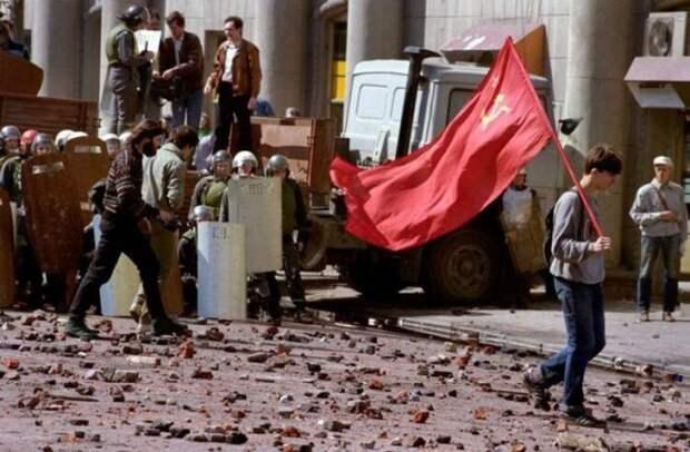 Одинокий демонстрант-коммунист, идущий по усыпанной камнями улице после кровопролитного столкновения с правоохранительными органами,1993 год СССР, прошлое, фото