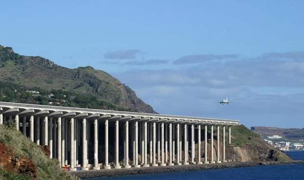 Мадейра Аэропорт Фуншала Изначально в аэропорту Мадейры было две взлетно-посадочных полосы, протяженность каждой из которых составляла 1600 метров. Но после авиакатастрофы в 1977 года, в результате которой погиб 131 пассажир, инженеры, наконец, осознали, что такой длины не вполне достаточно для маневров и удлинили полосы на 200 метров. Подобное преобразование не сильно улучшило условия взлета и посадки, и в 2000 году было принято решение достроить полосу, разместив ее часть на 180 железобетонных опорах. Необычную конструкцию дополняет разнообразный ландшафт: с одной стороны аэропорта находится море, с другой — горы, что требует от пилотов определенной сноровки при выполнении маневров.