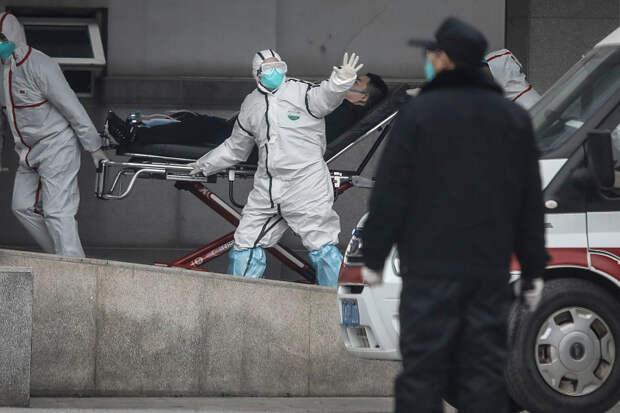 Врачи в масках и защитных очках транспортируют пациента, больница города Ухань, 17 января 2019 года / © Getty Images