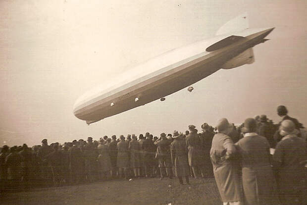 A black-and-white (sepia) image of a cigar-shaped airship flying from right to left over a crowd of people. Four of its five engines and the gondola are visible, as is the registration D-LZ127.