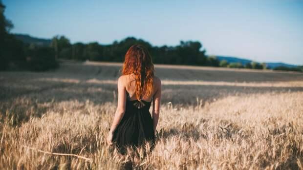 Девушка стоит спиной в поле