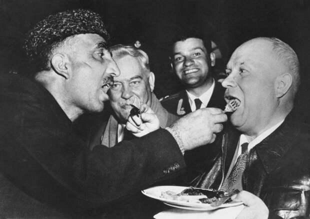 Никита Хрущев и премьер-министр индийского штата Кашмир Бакши Гуллям Мохаммад кормят друг друга по старинной кашмирской традиции во время визита Хрущева в Индию, 1955