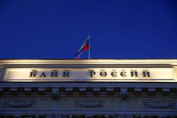 """A Russian state flag flies over the Central Bank headquarters in Moscow, Russia March 29, 2021. A sign reads: """"Bank of Russia"""". REUTERS/Maxim Shemetov"""