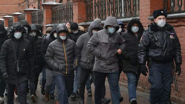 Сотрудник полиции выстраивает в очередь мигрантов у здания УФМС - РИА Новости, 1920, 16.12.2020