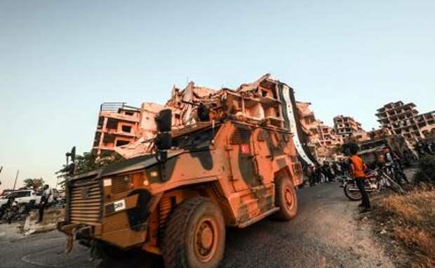 На фото: турецкая военная машина проезжает мимо сирийцев, собравшихся на антисирийскую правительственную демонстрацию, у руин здания, украшенного гигантским флагом сирийской оппозиции, провинция Идлиб