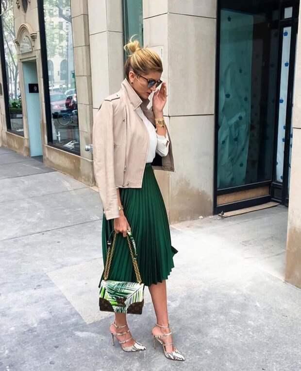 Девушка в зеленой юбке миди и бежевой куртке косухе