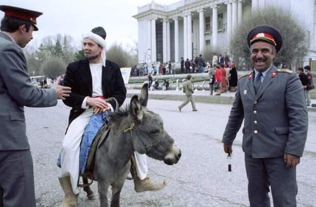 Таджикские милиционеры беседуют с участником празднования навруза, одетым в костюм Ходжа Насреддина, перед театром имени Камола Худжанди в Ленинабаде, 1990 год.
