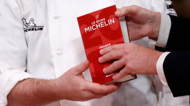 красный гид мишлен в руках шеф-повара