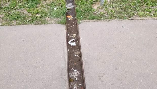 Рабочие очистили от мусора газон на Тепличной улице в Подольске