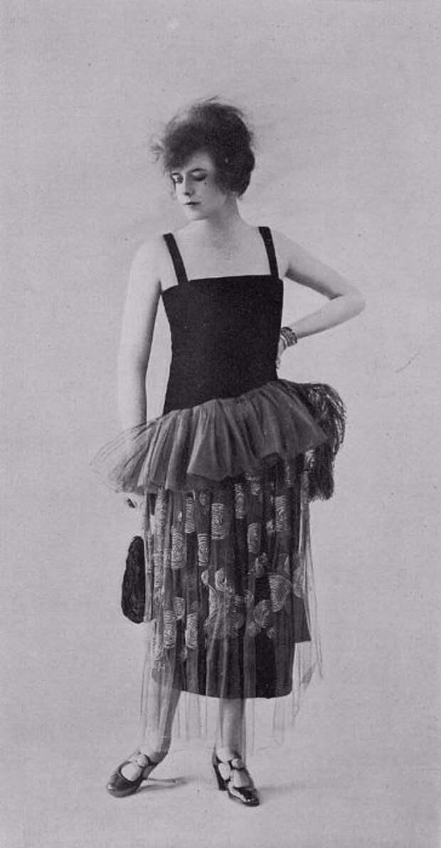 Женщина в черном платье с отделкой по краям и перьями.