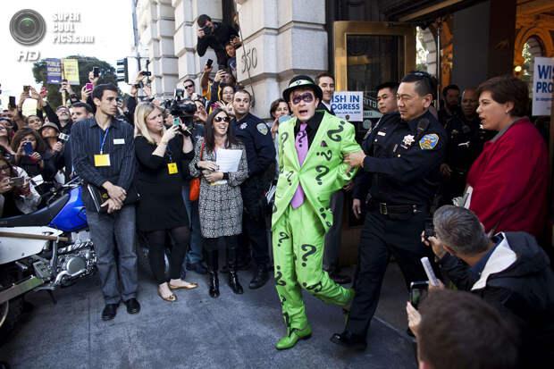 США. Сан-Франциско, Калифорния. 15 ноября. Пойманный Бэткидом суперзлодей Загадочник покидает «место преступления». (Ramin Talaie/Getty Images)