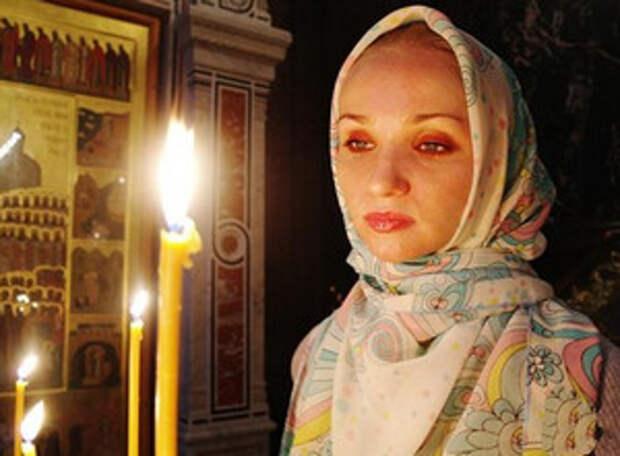 Девушка в платке ставит свечку