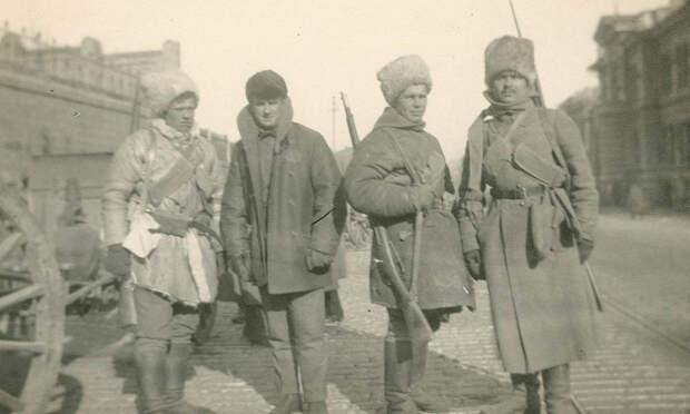 Бойцы в зимнем обмундировании на улицах города. Экипированы кто как может.