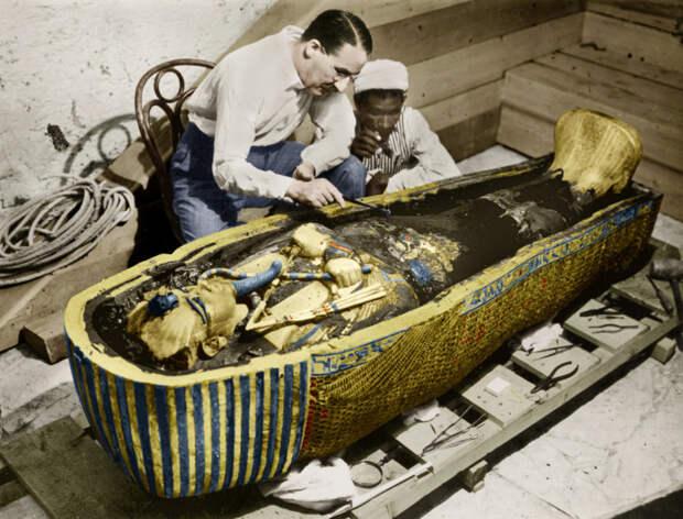 20. Археолог Говард Картер исследует золотой саркофаг Тутанхамона после открытия гробницы Тутанхамона в 1923 году. история, мир, фотография