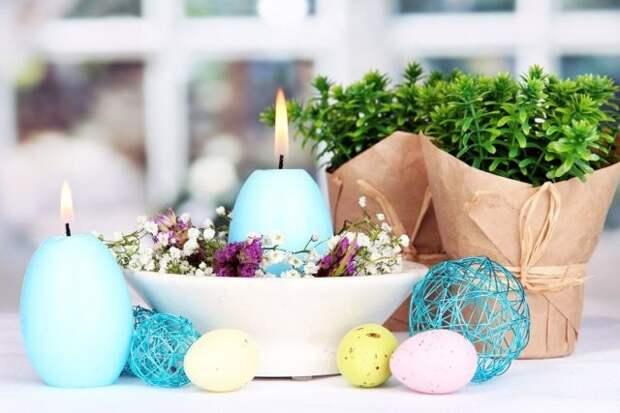 голубые свечи в форме яйца на столе