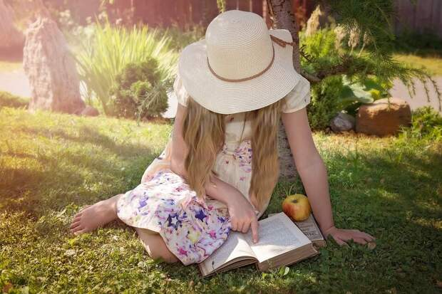 На фото девочка в шляпе читает книжку на траве.