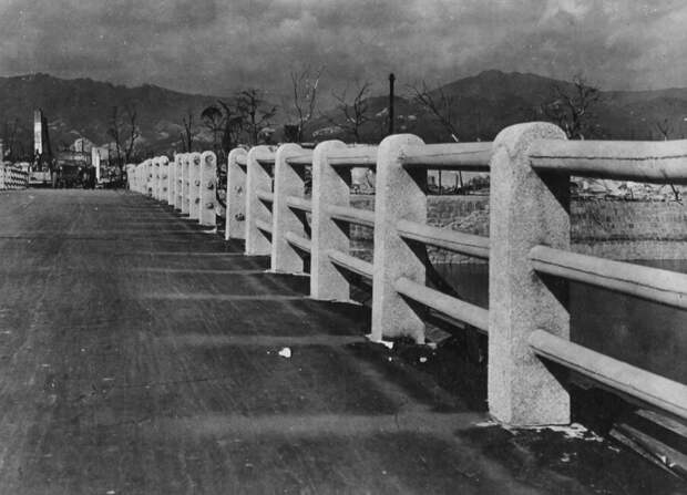 12. Мост через реку Ота в 880 метрах от гипоцентра взрыва над Хиросимой. Заметьте, как сгорела дорога, и слева видны призрачные отпечатки там, где когда-то поверхность защищали бетонные колонны. (U.S. National Archives)