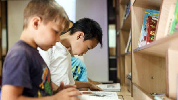 Школьники читают книги в библиотеке, архивное фото