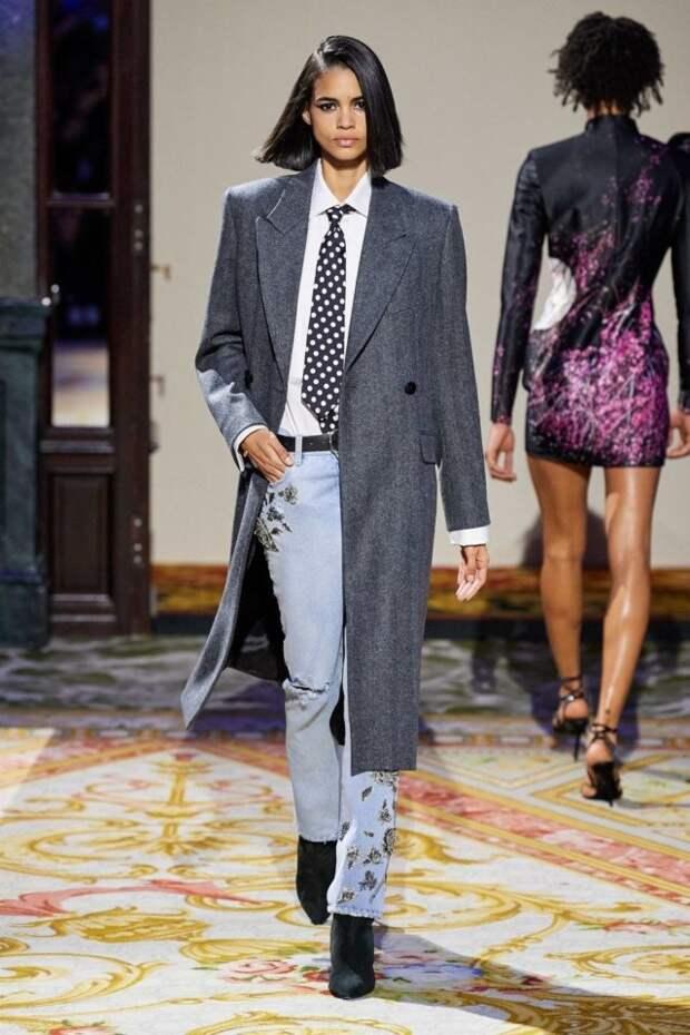 модель в пальто, джинсах и галстуке на подиуме
