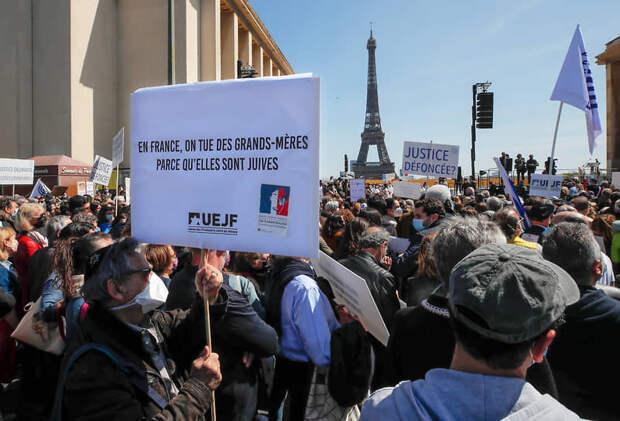Участник митинга держит табличку с надписью «Во Франции убивают пожилых женщин, потому что они еврейки»